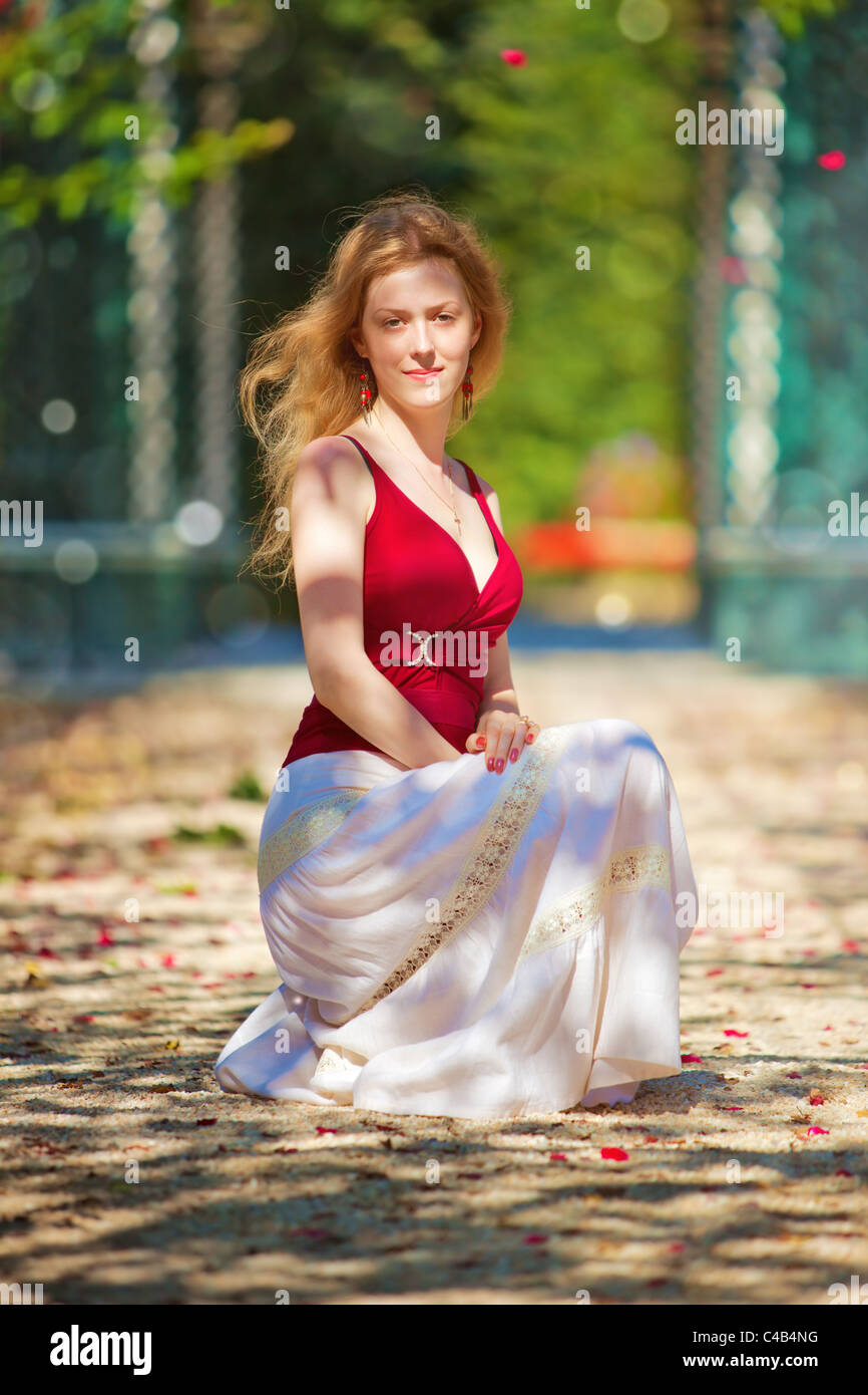 Young woman in a park with falling petals. - Stock Image