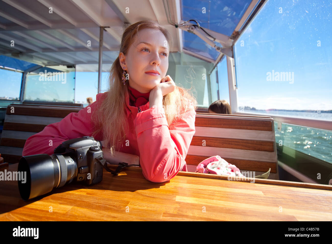 Young woman tourist aside on sea. - Stock Image