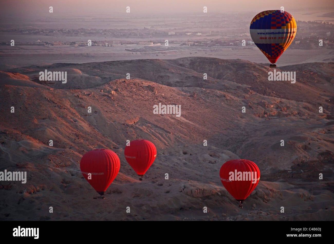 multicoloured hot air balloons, ascend at dawn over the Valley of the Kings and Queens, Al Asasif, Luxor, Egypt - Stock Image