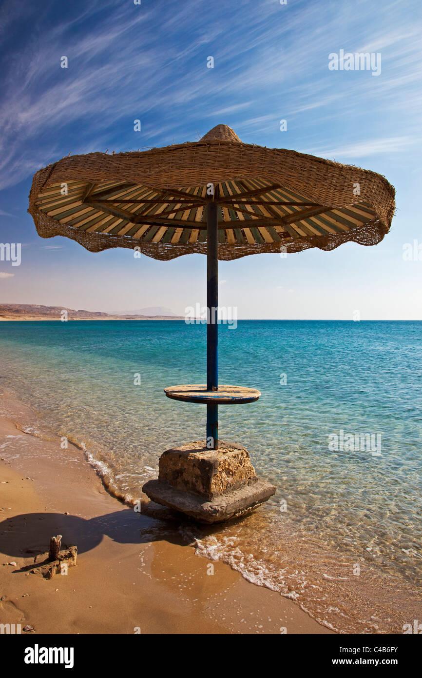 Sun umbrella on the beach at makman el Tiyha, Janub Sina, Gulf of Suez, Red Sea, Sinai Peninsula, Egypt Africa. - Stock Image