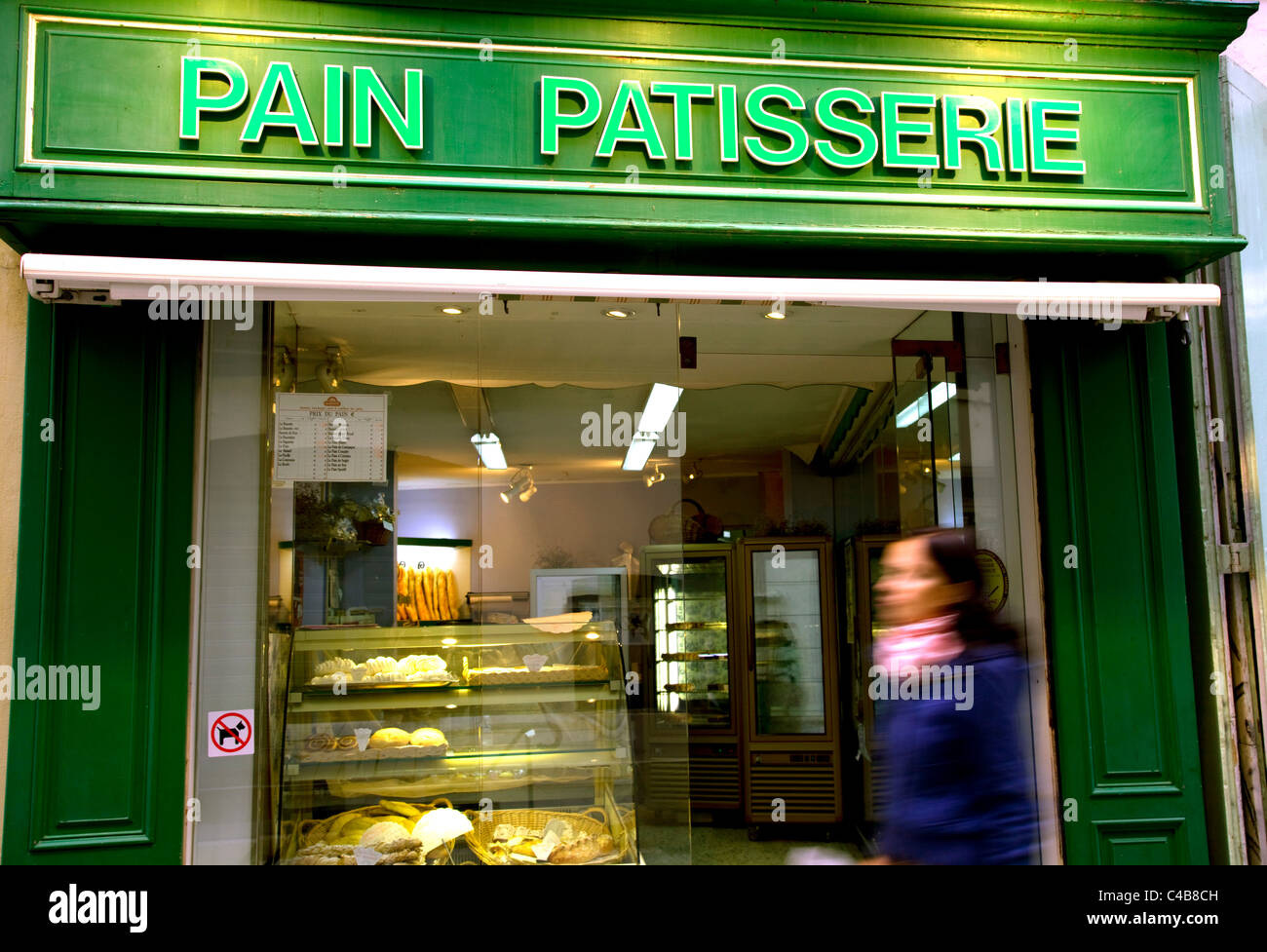 Arles; Bouches du Rhone, France; Young woman walking in front of a brightly coloured facade of a 'pain patisserie' Stock Photo