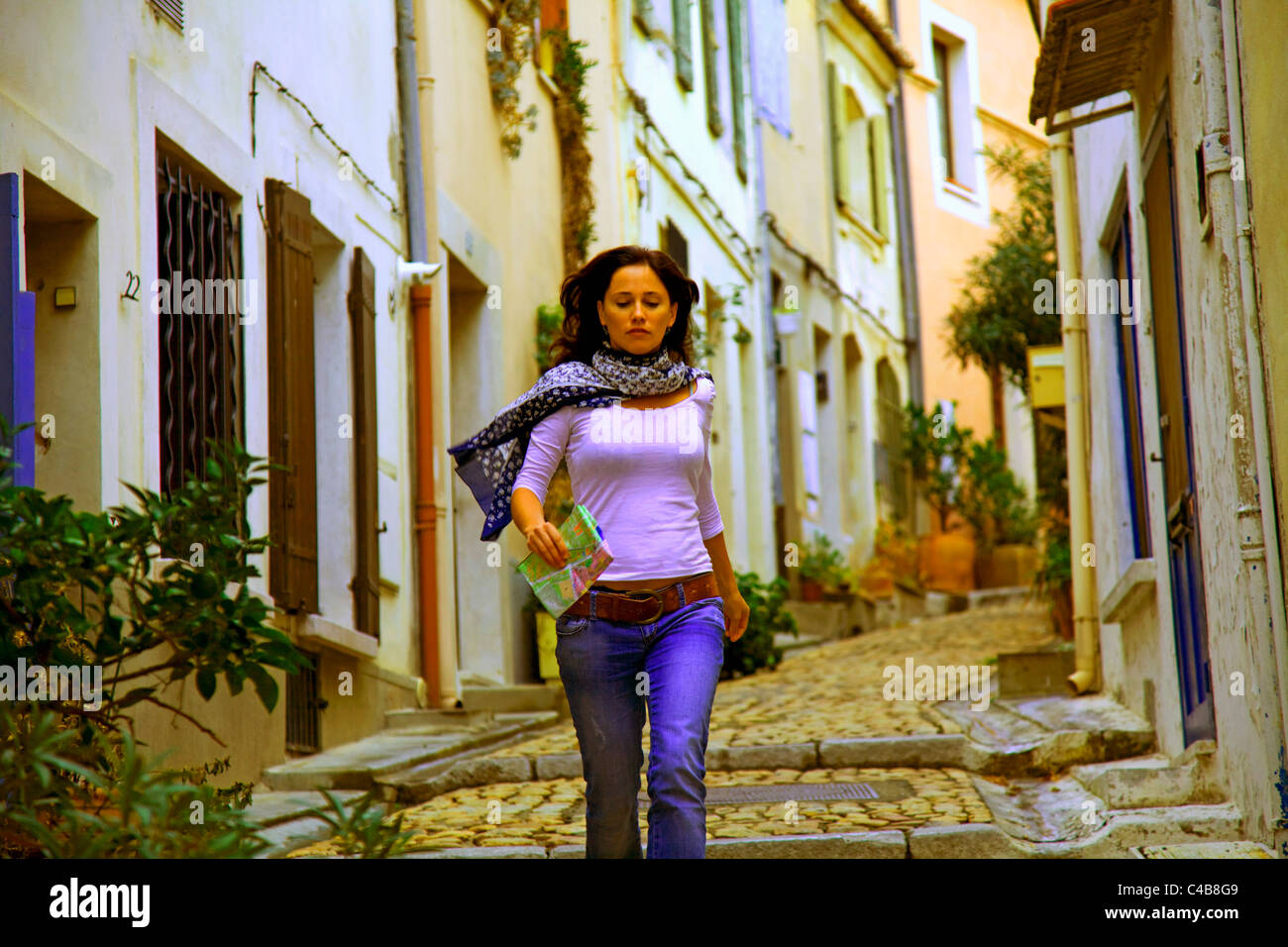 Arles; Bouches du Rhone, France; A young woman walking down the cobbled streets of the Town. MR. Stock Photo