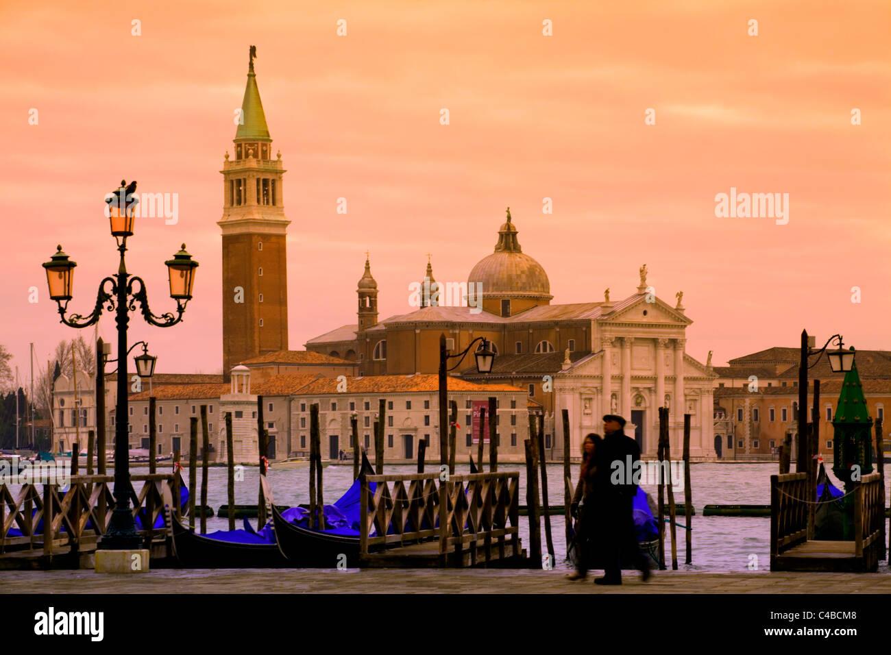 Venice, Veneto, Italy; A couple walking on the bacino di San Marco onlooking San Giorgio Maggiore - Stock Image