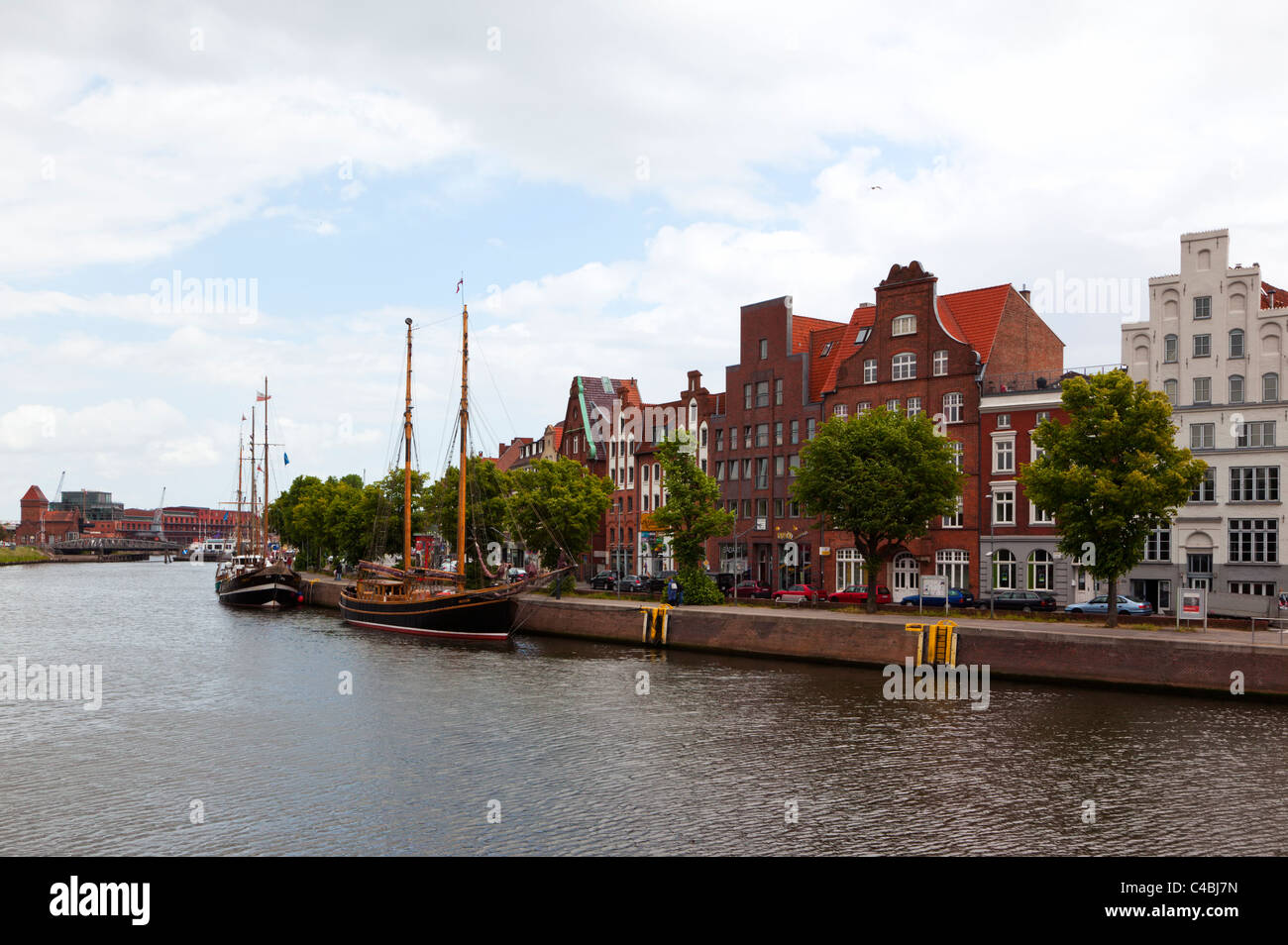 historic facades and museum ships at the Untertrave pier, Lubeck - Stock Image