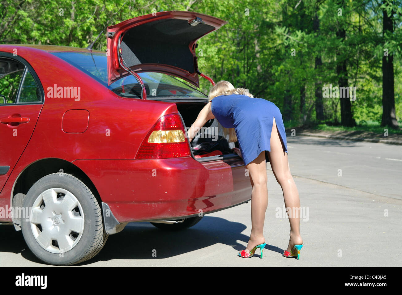 The girl the blonde searches for tools in a luggage carrier of the red car in the summer, Moscow - Stock Image