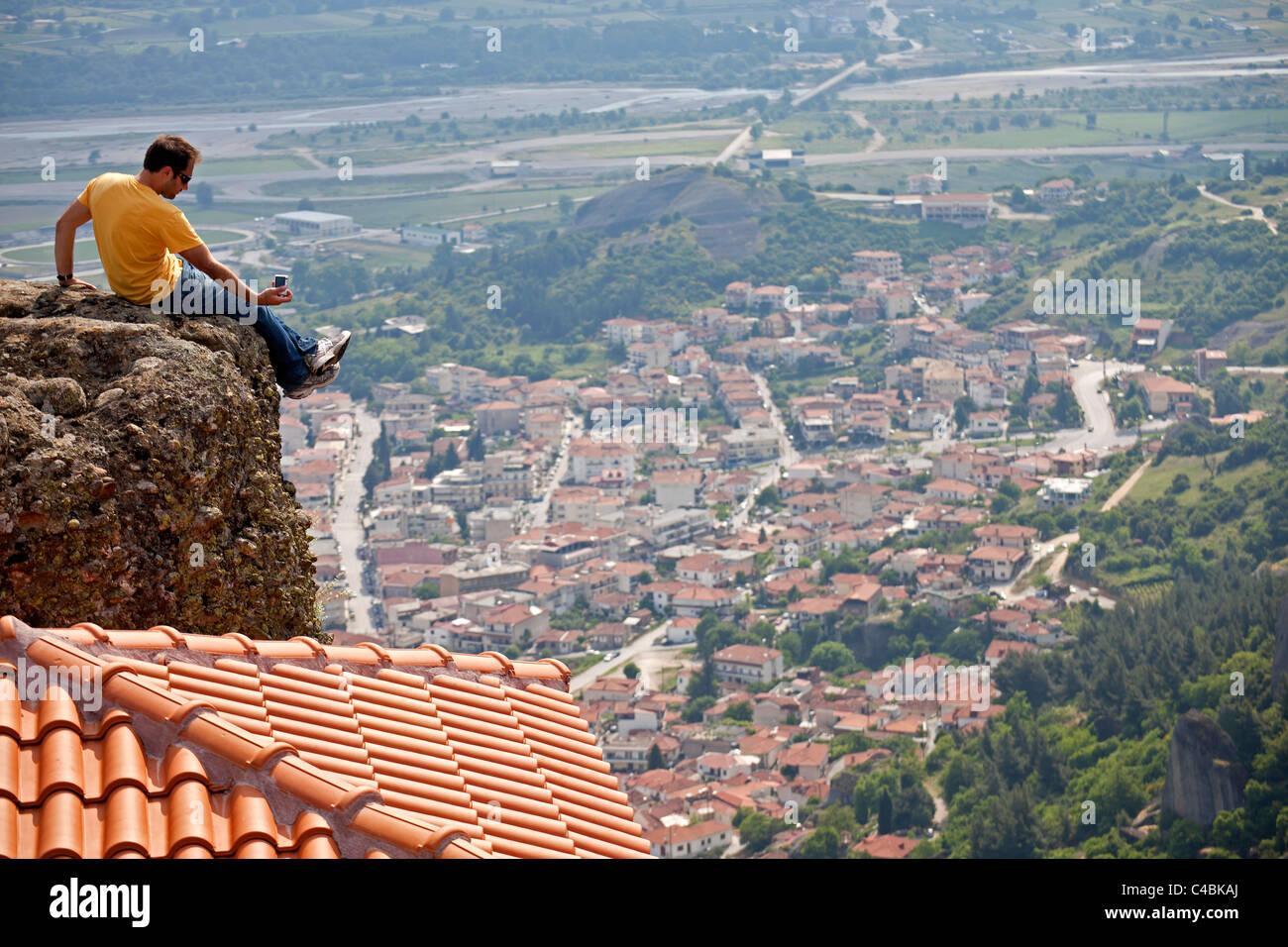 Man above the monastery Agia Triada taking pictures of the town Kalambaka. Meteora, Greece - Stock Image