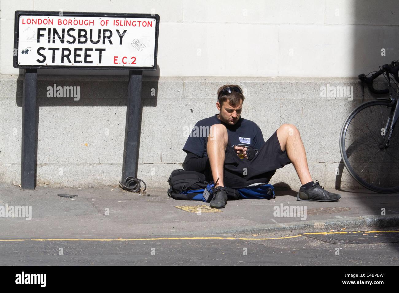 cycle bicycle bike messenger taking a break, in London - Stock Image