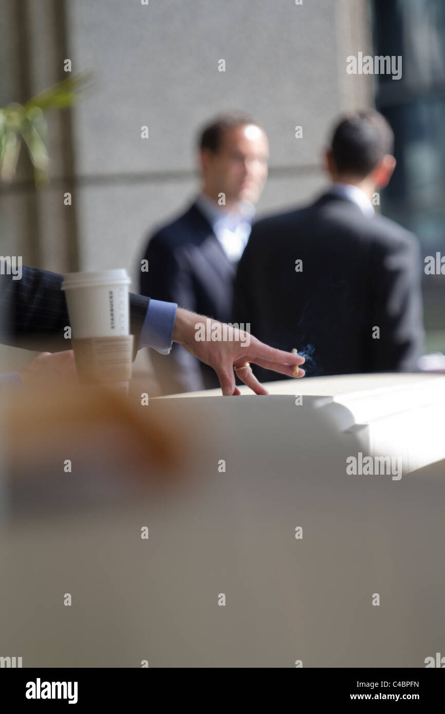 smoker taking break outside offices City of London - Stock Image