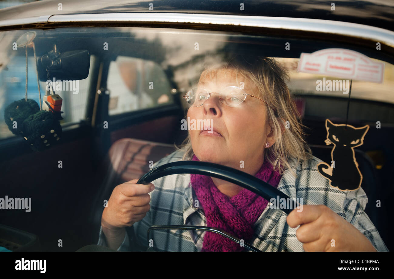 Concentrated and stressed senior woman driving an oldtimer car - Stock Image