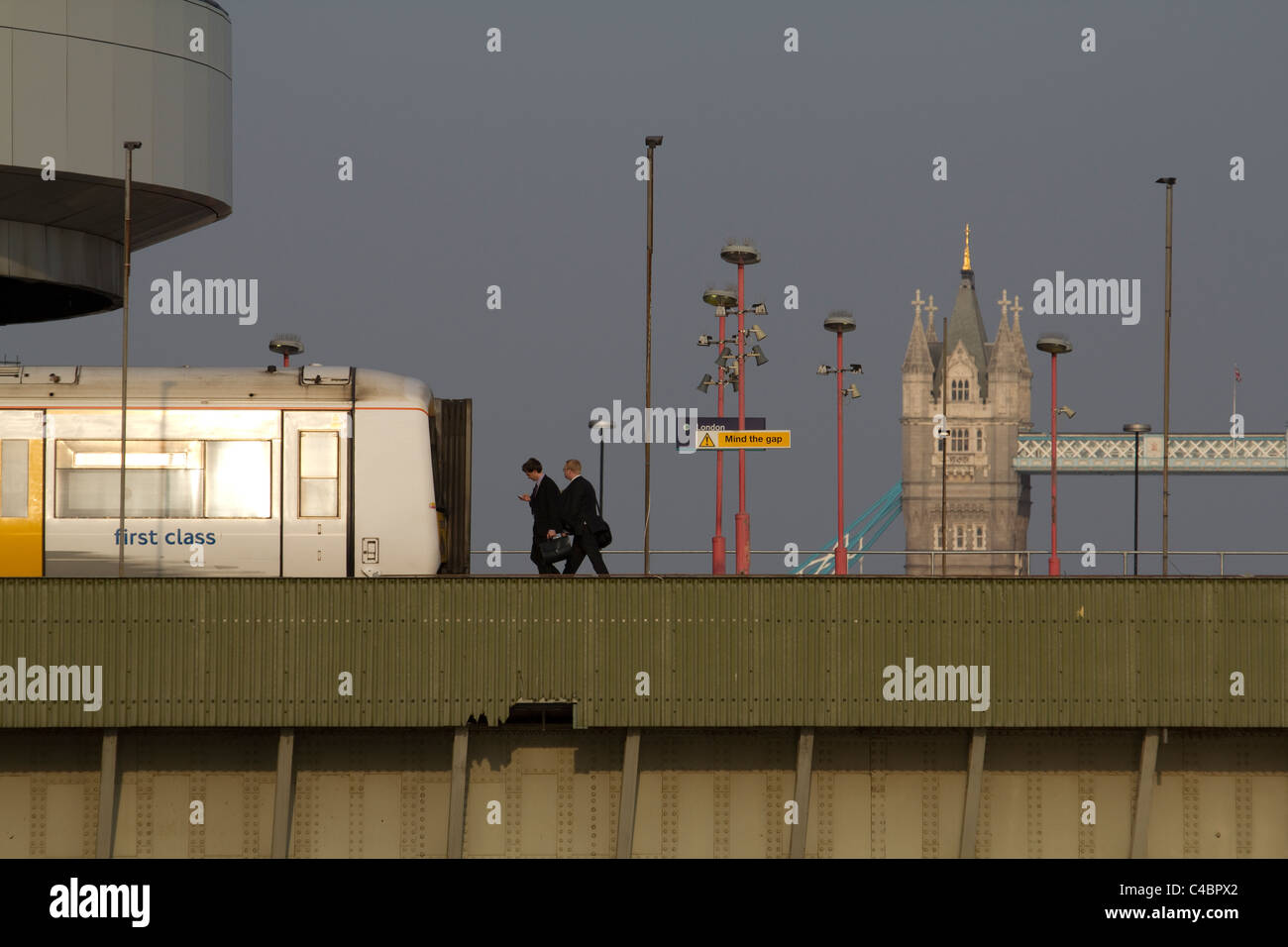 london commuters walk to first class train on London Cannon Street station Railway Bridge, with Tower Bridge in - Stock Image