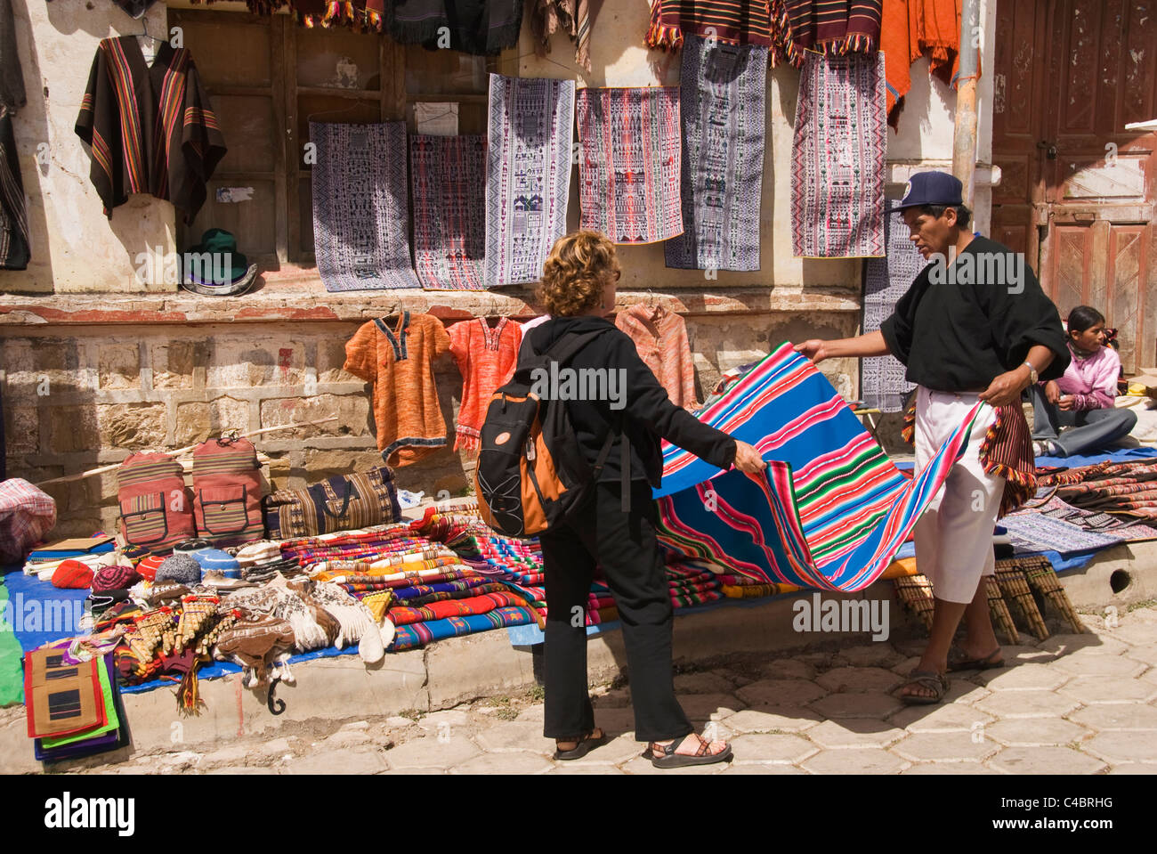 Tarabuco, Sunday market, Western woman looking at textiles for sale - Stock Image