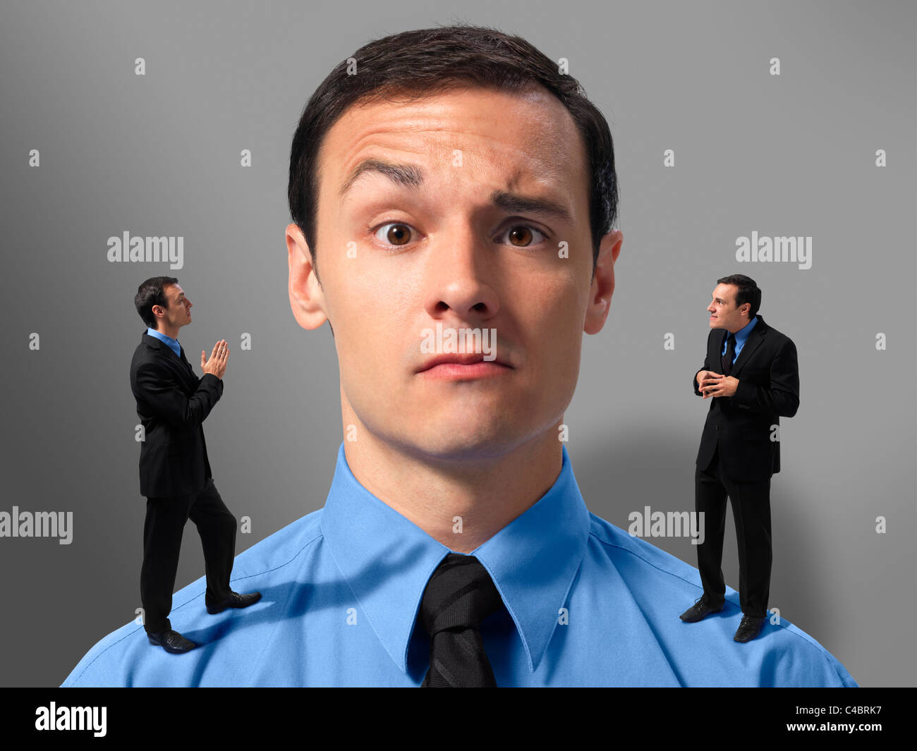 Businessman making decision symbolized by angel and devil versions of himself on his shoulders - Stock Image