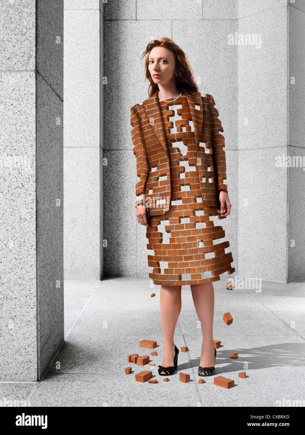 woman made of bricks that are breaking apart, standing in outdoor plaza with granite columns - Stock Image