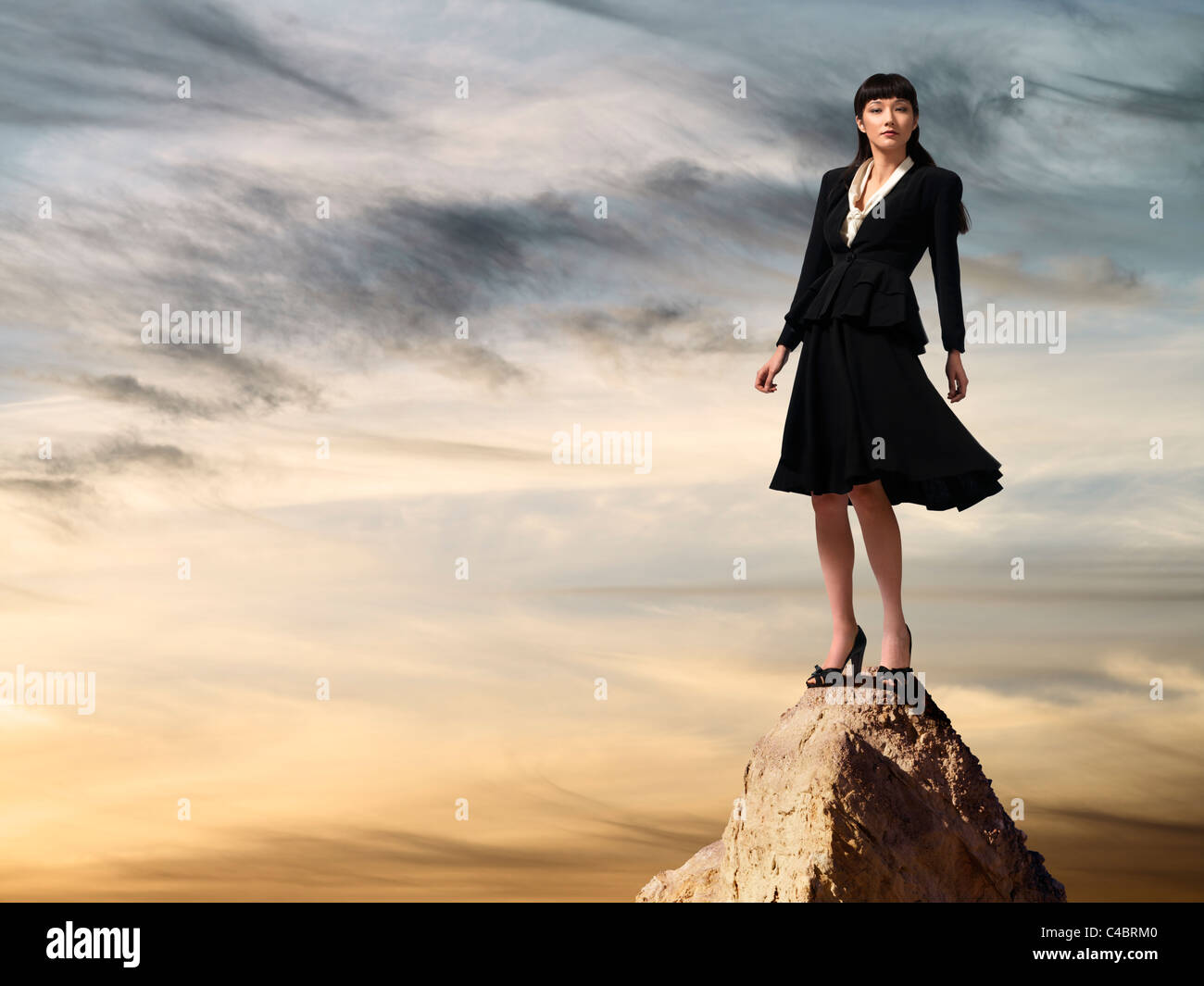 Asian business woman standing on mountaintop at sunset - Stock Image