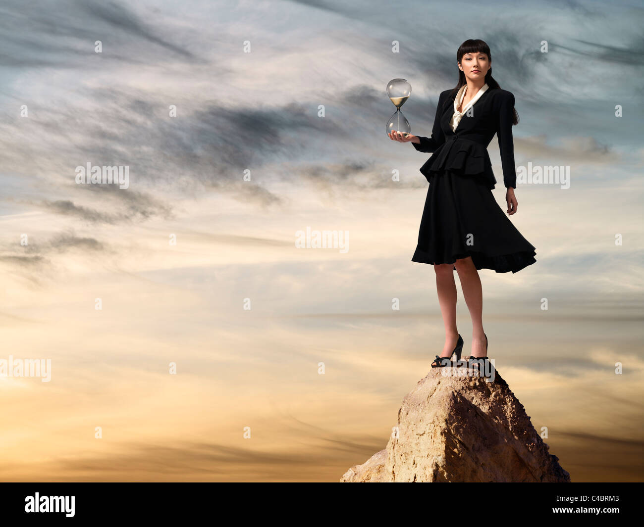 Asian business woman holding hourglass standing on mountaintop at sunset - Stock Image