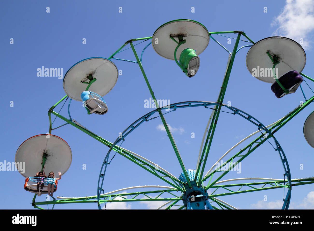 Florida Palatka Blue Crab Festival annual event carnival ride whirling swing girl girls wave Black - Stock Image