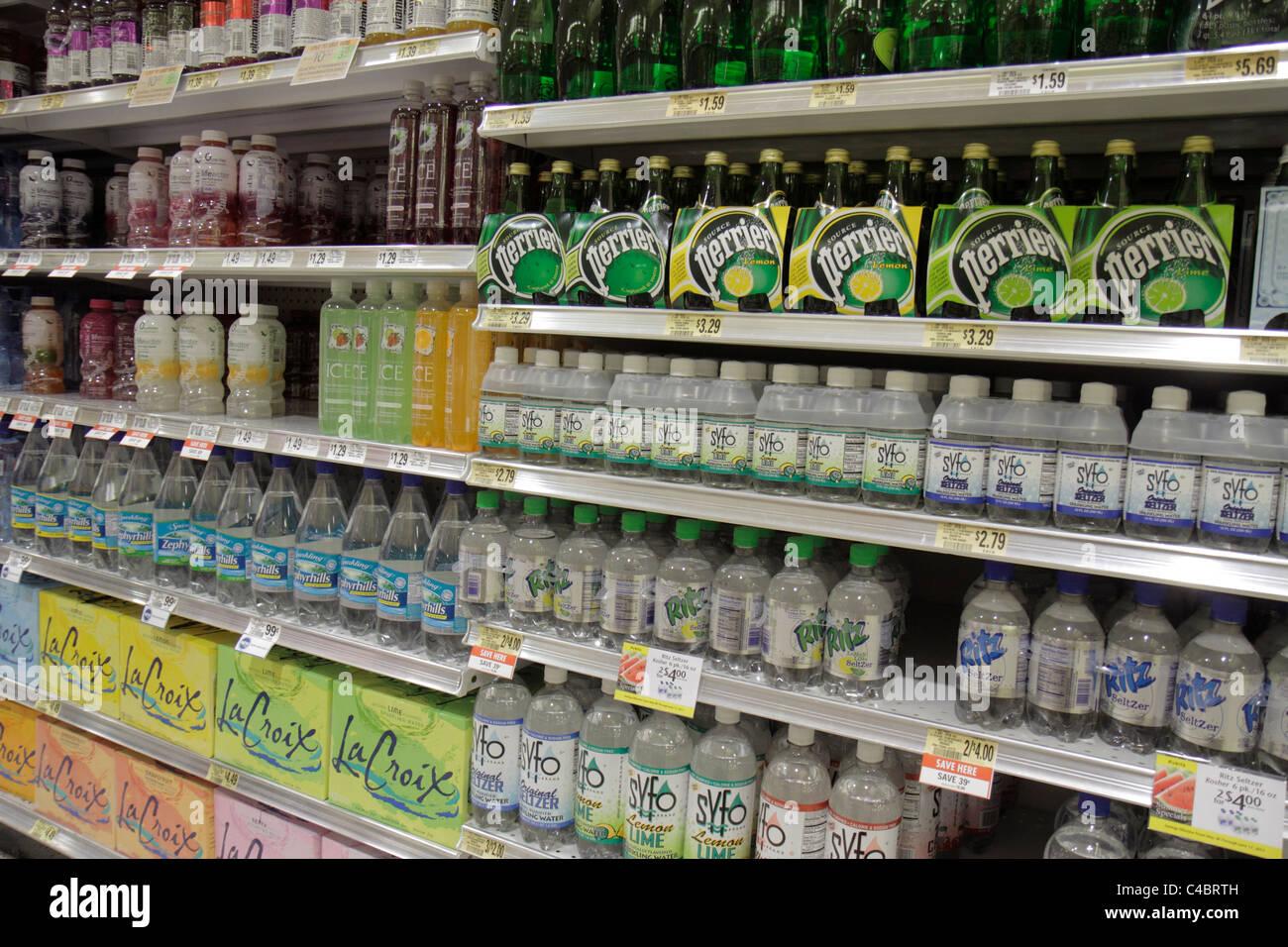 Ocala Florida Publix grocery store supermarket retail display packaging competing brands bottled water shelf shelves - Stock Image