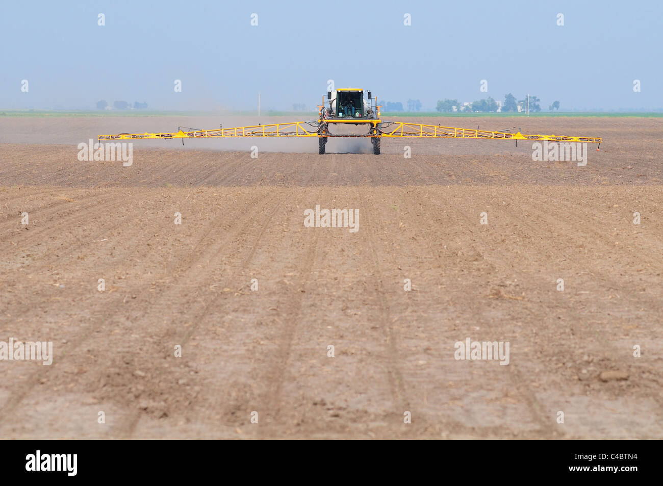 Self propelled crop sprayer spraying herbicide or insecticide on a pre emergent farm field. - Stock Image