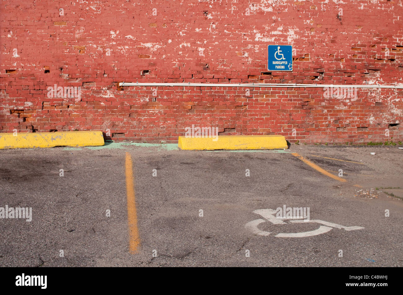 Handicapped/Disabled parking space in the USA against a brick wall in a parking lot. - Stock Image