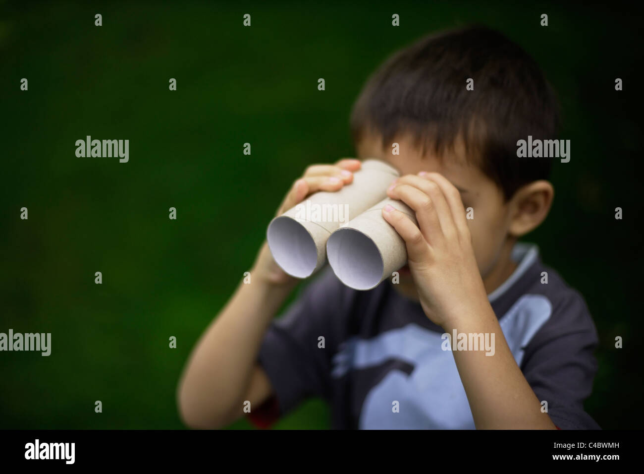 Six year old boy uses toilet cardboard tubes from toilet paper rolls as binoculars. Mixed race, indian athnic, caucasian - Stock Image