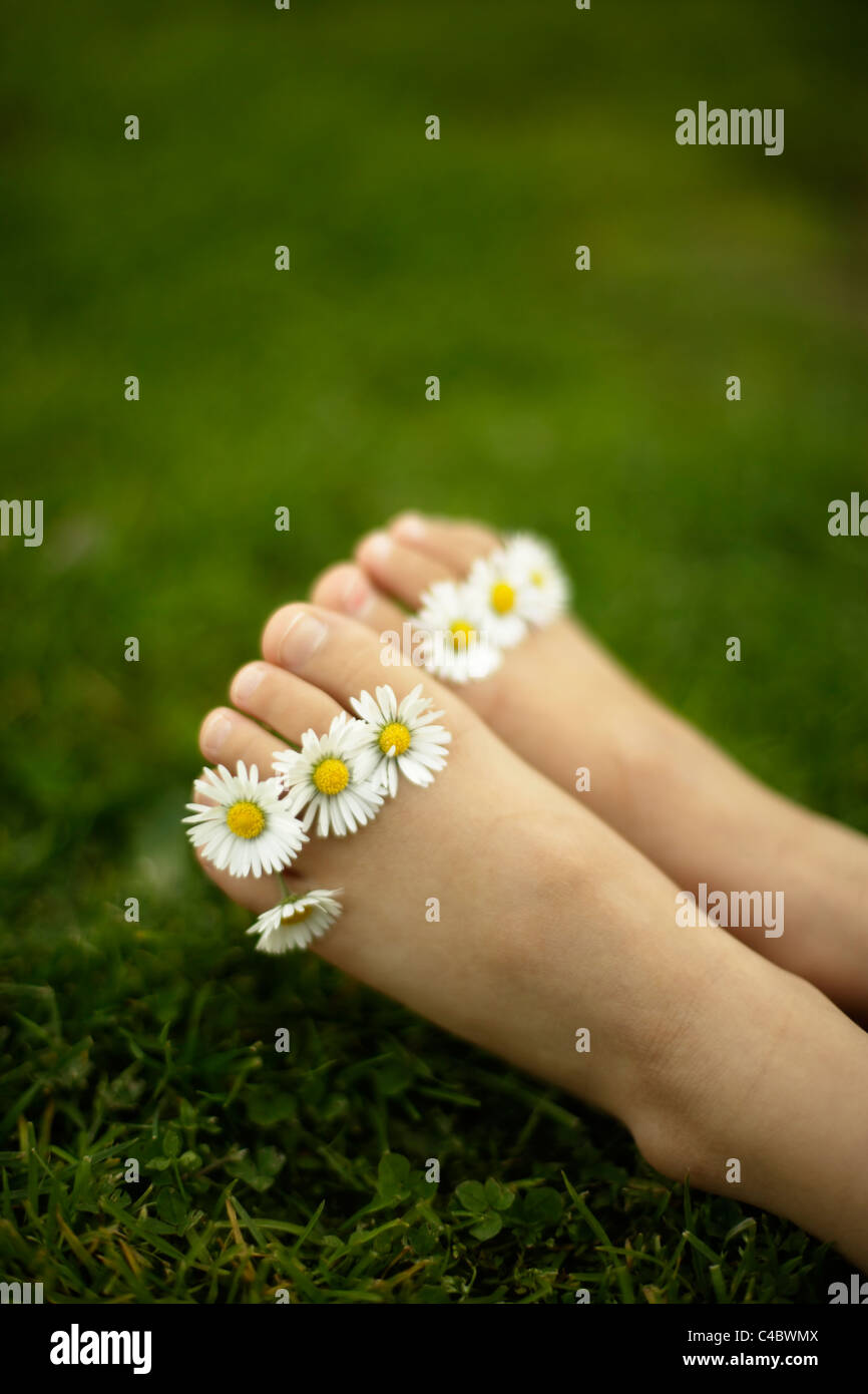 Five year old girl with daisies between her toes - Stock Image