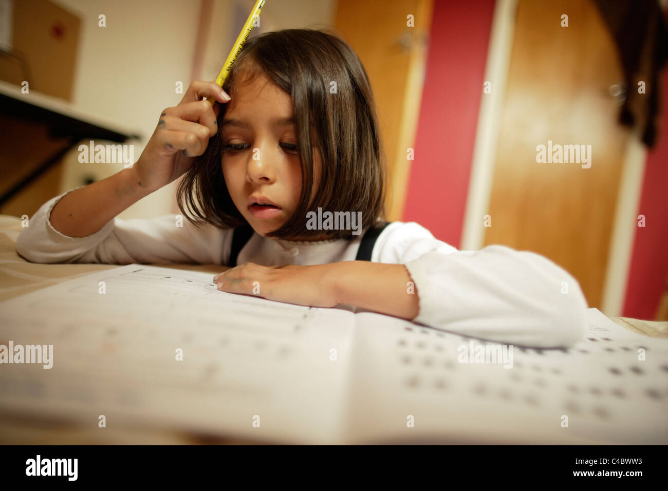 Girl does her music theory homework. - Stock Image
