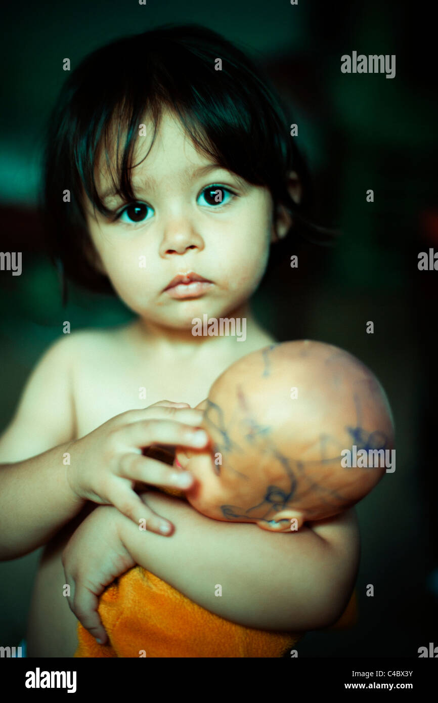 Two year old girl holds her battered much-loved doll - Stock Image