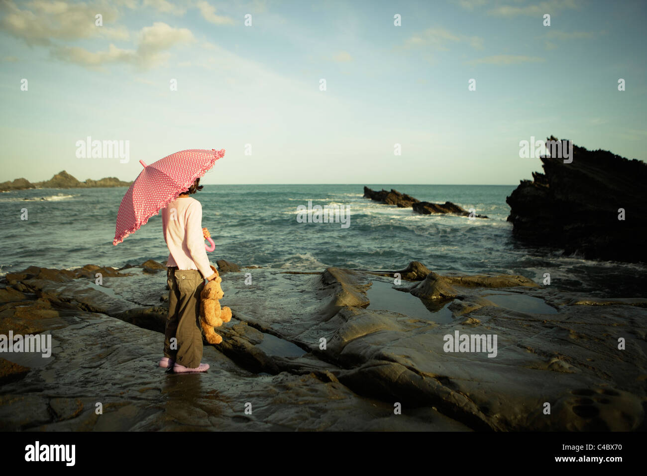 Girl with pink umbrella and teddy bear, Cape Palliser, New Zealand - Stock Image