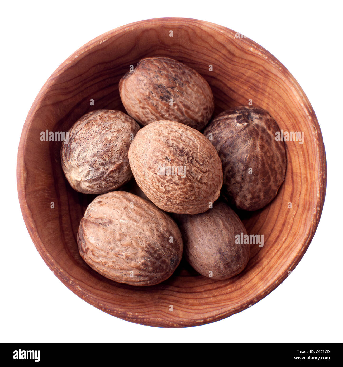 Nutmeg in a wooden bowl isolated on white Stock Photo