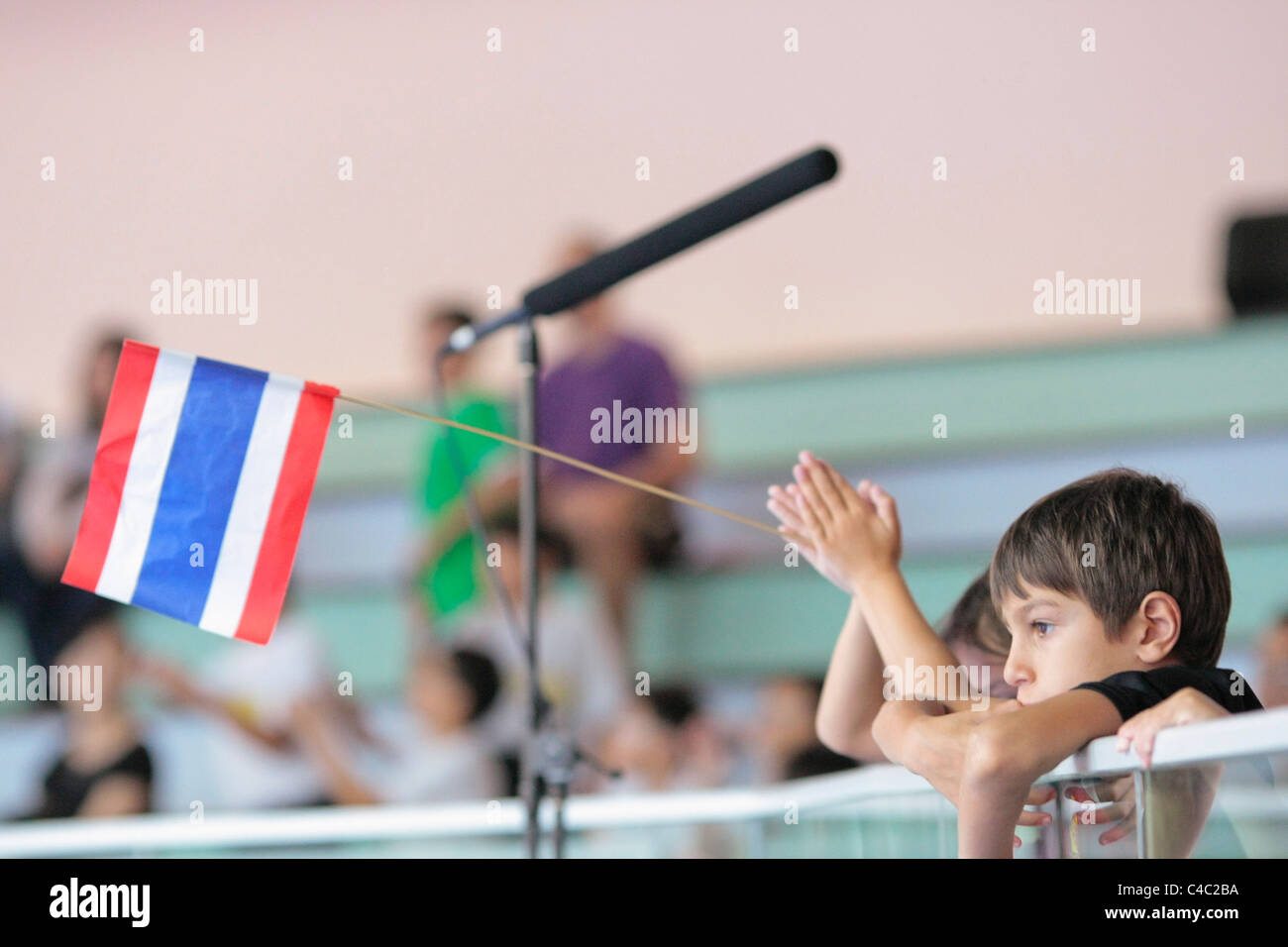 Thai fans waving the state flag of Thailand. - Stock Image