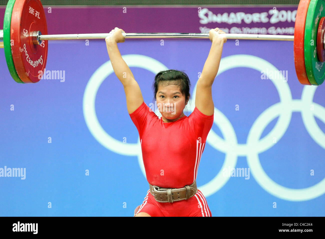 Dewi Safitri of Indonesia in action during her clean and jerk routine. - Stock Image