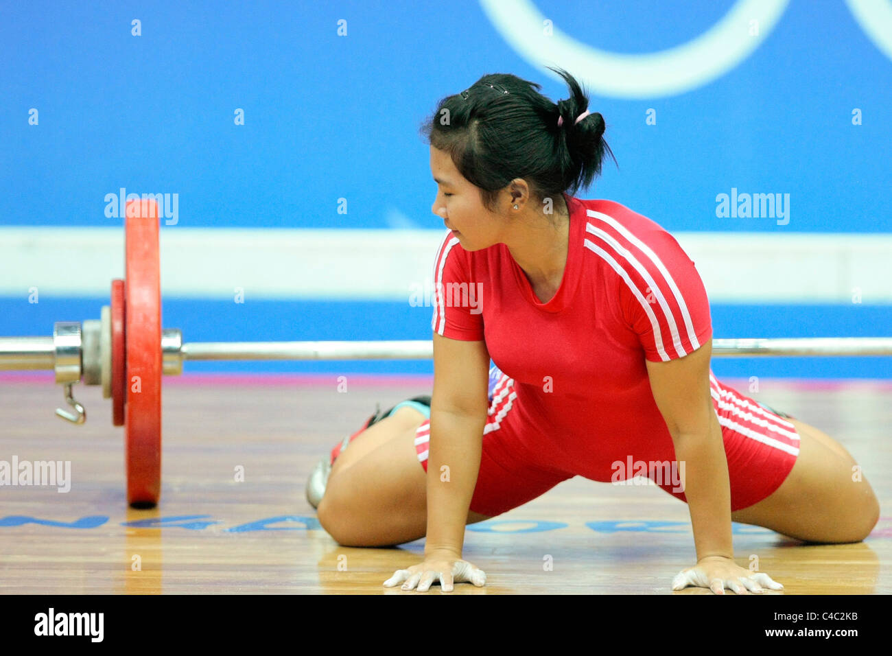 Dewi Safitri of Indonesia in down on the ground after failing to lift during her snatch routine. - Stock Image