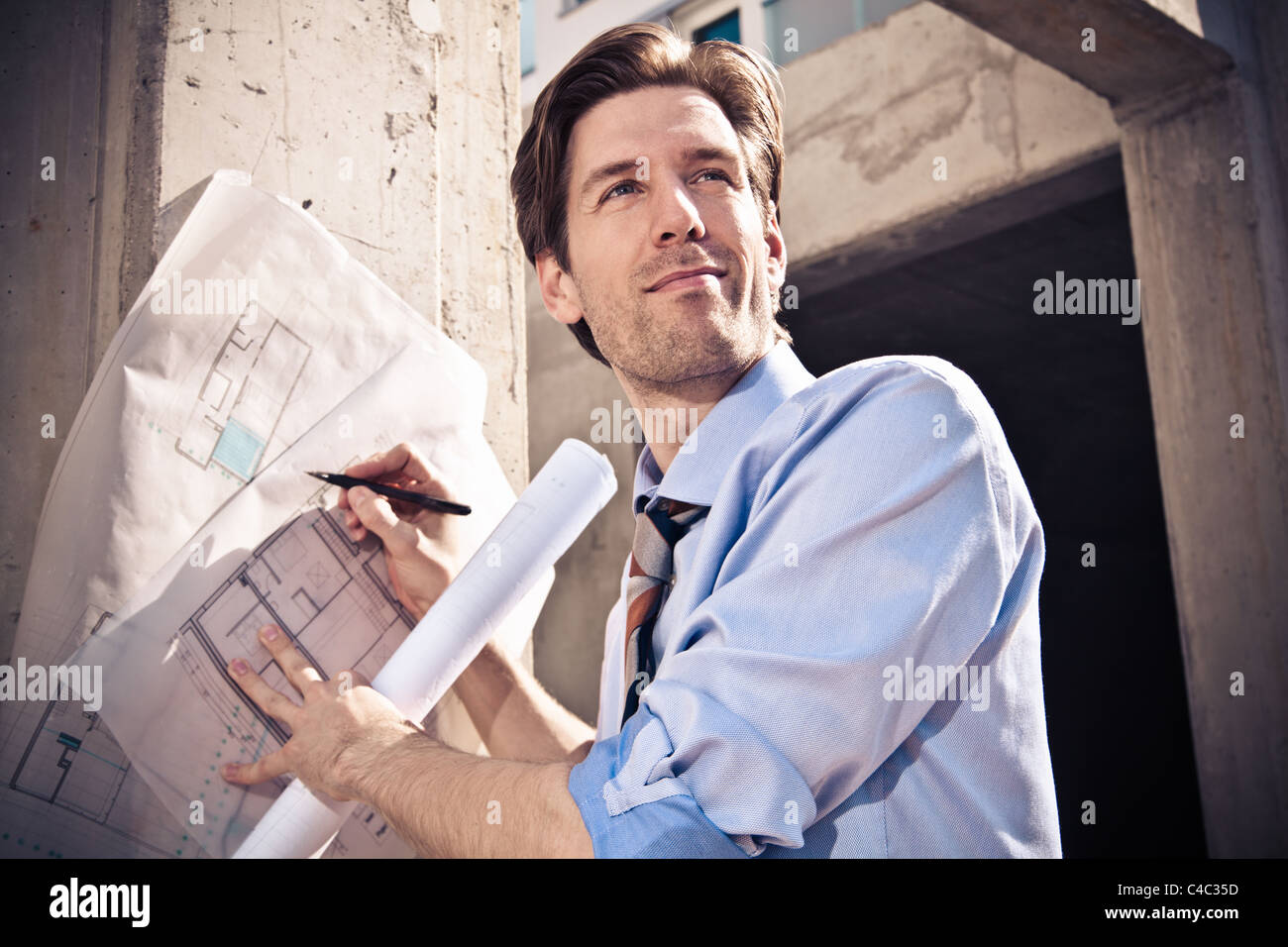 Businessman with blueprints on site - Stock Image