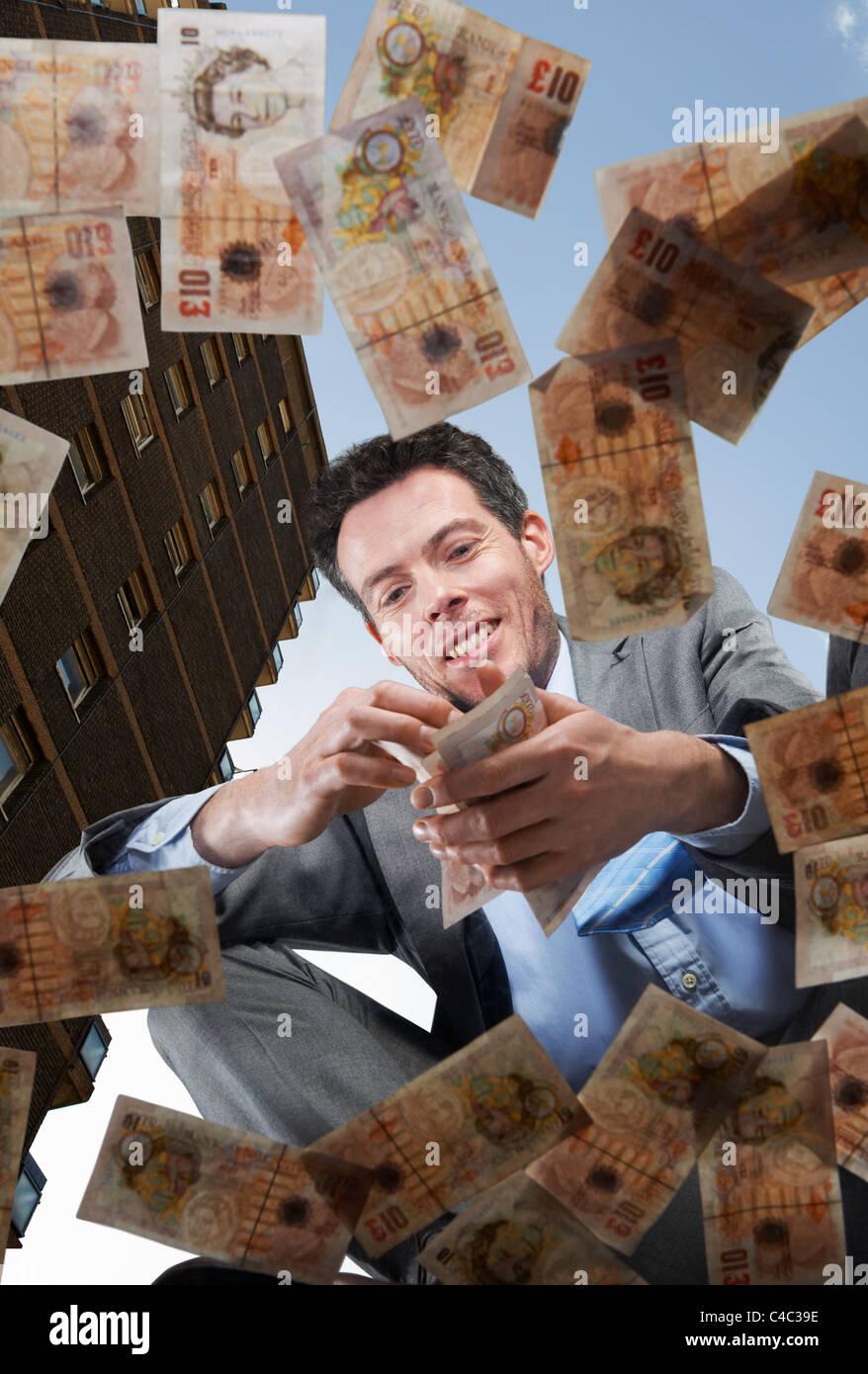 Businessman picking up discarded money - Stock Image