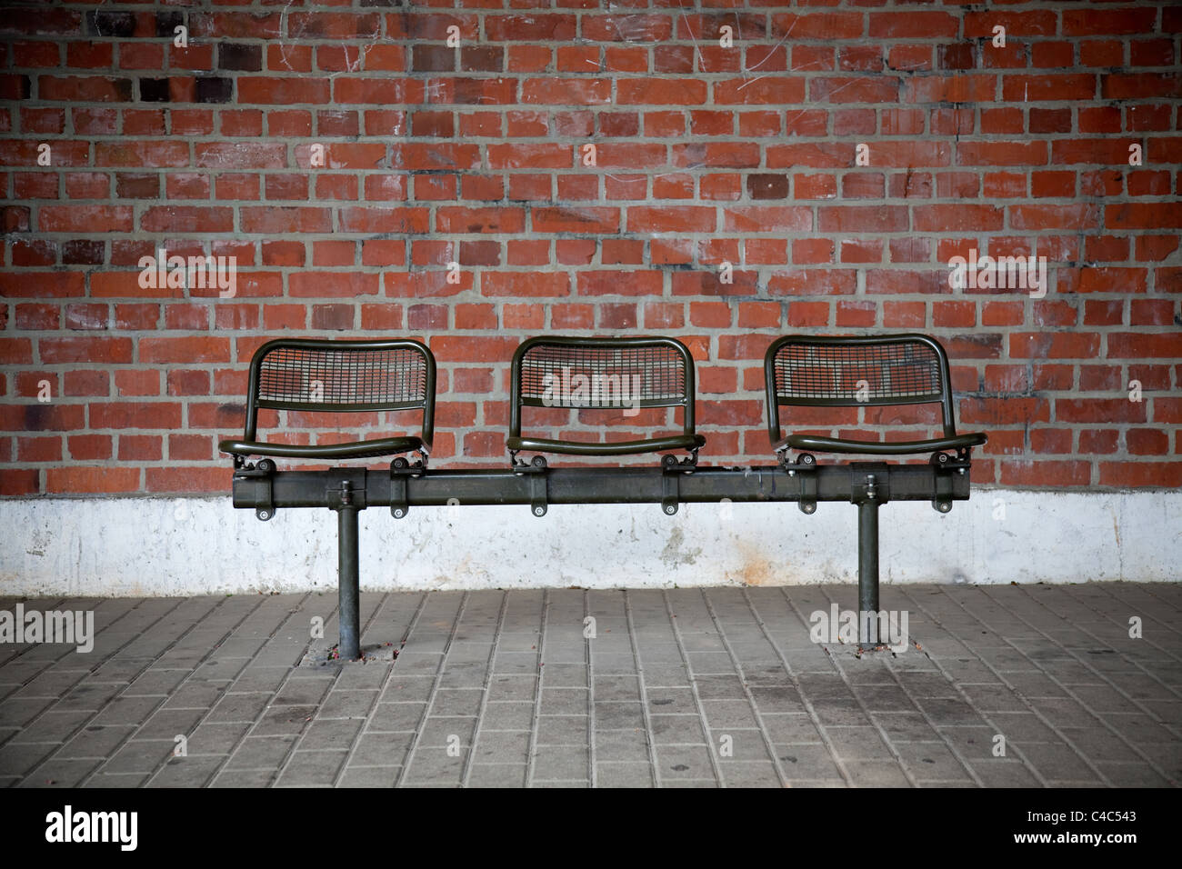 a bench with three seats in front of a brick wall - Stock Image