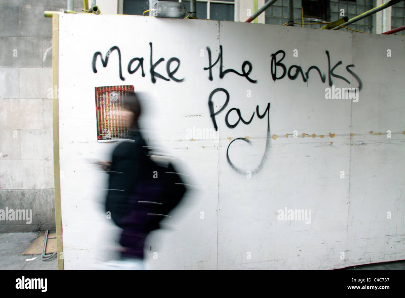 Woman walking past anti-capitalist graffiti in London demanding the banks pay for the national deficit - Stock Image