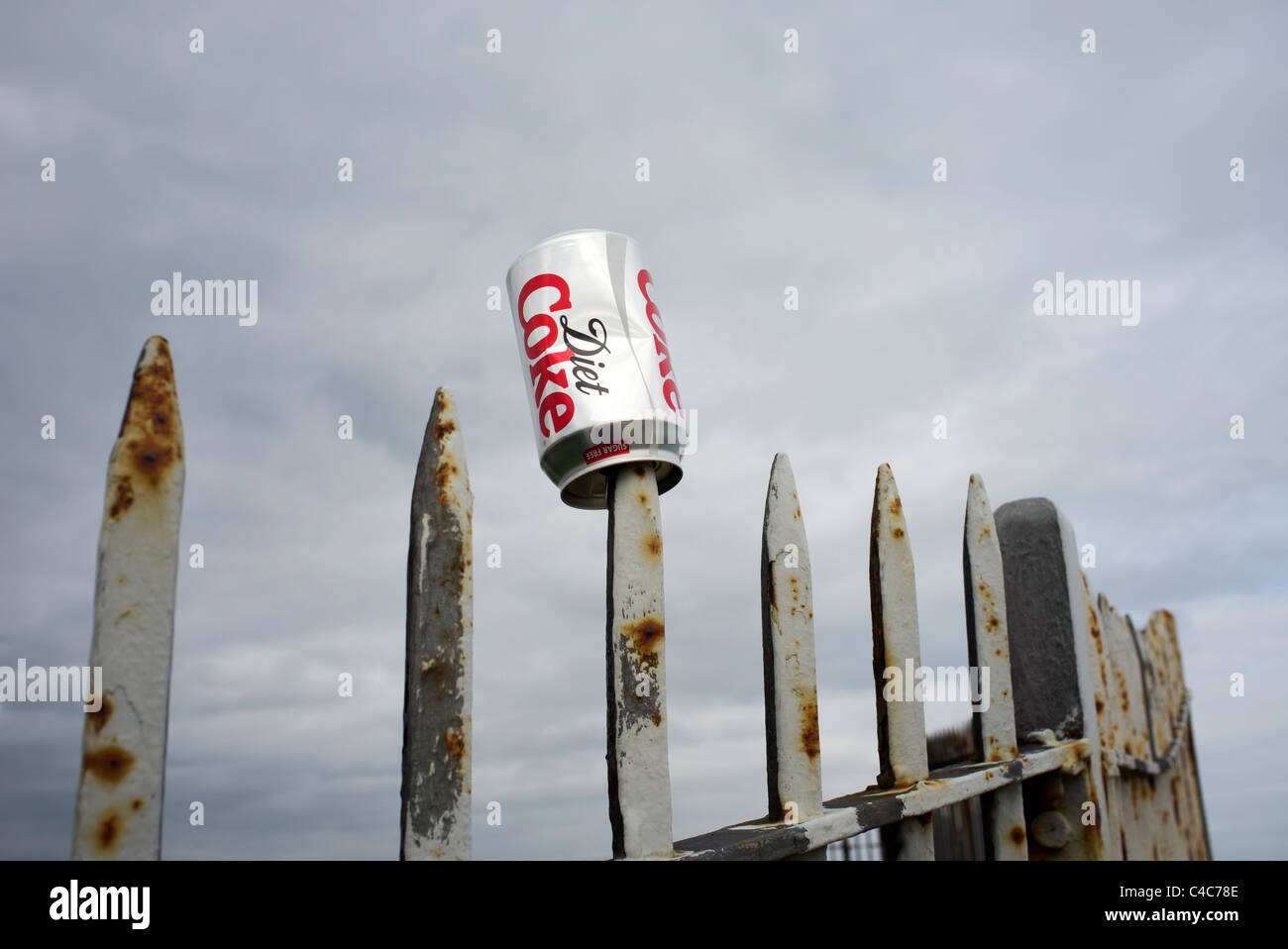 metal railings with a coke can impaled on the spikes - Stock Image