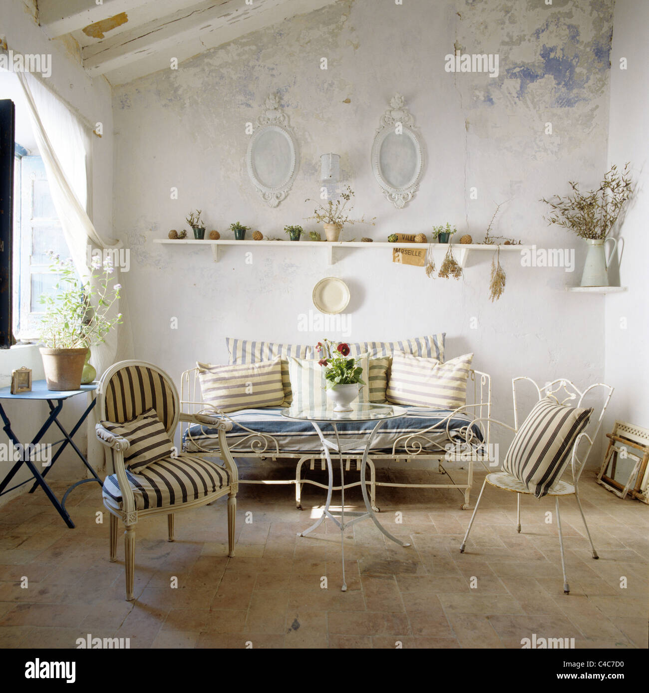 Living room with whitewashed walls wrought iron furniture and striped upholstered louis xv chair