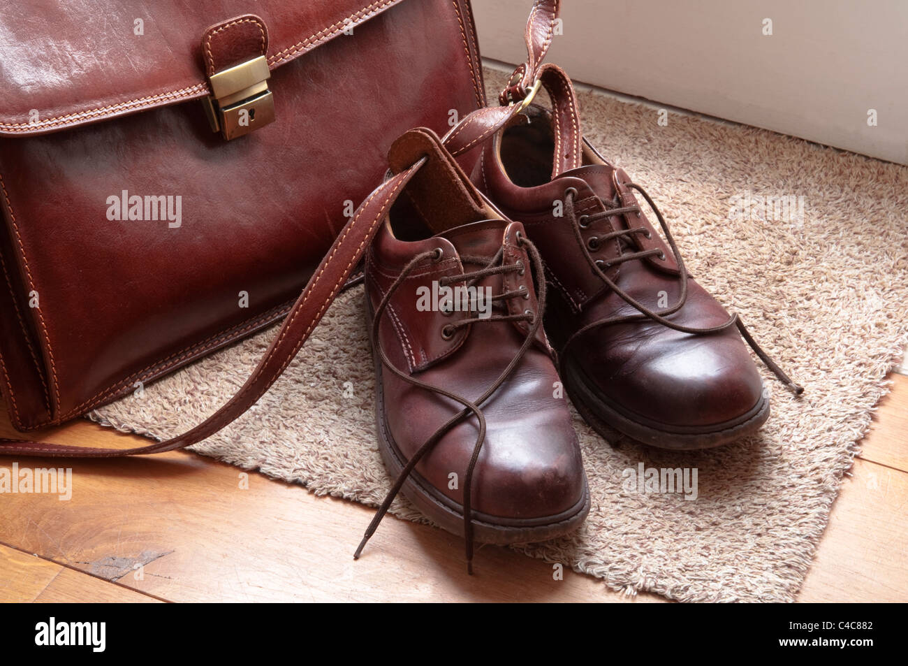Brown leather shoes and briefcase on a doormat by a door. UK - Stock Image