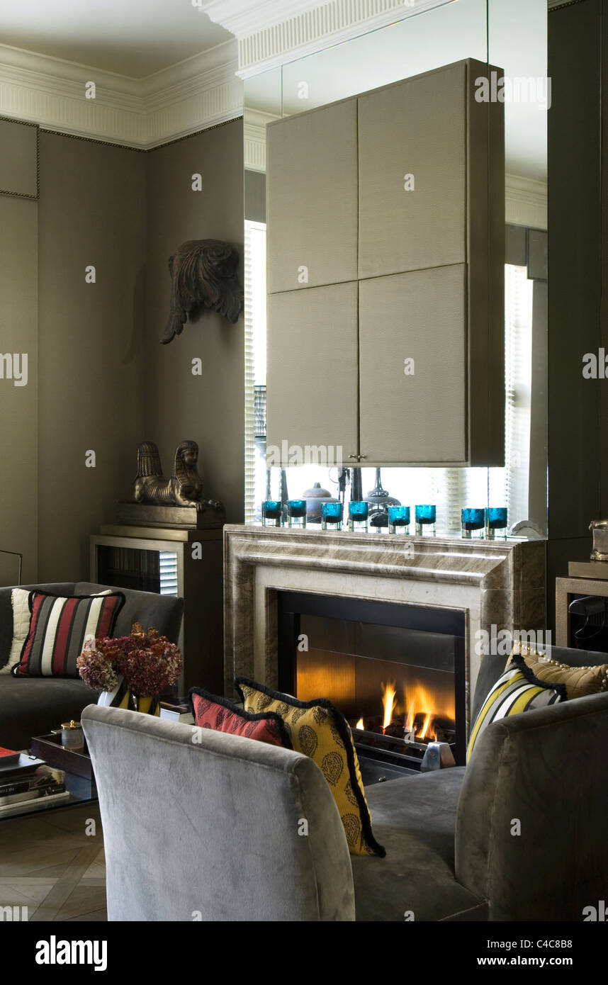 Grey suede daybed in living room with fireplace and mounted silk taffeta piece by Dominique Kieffer - Stock Image