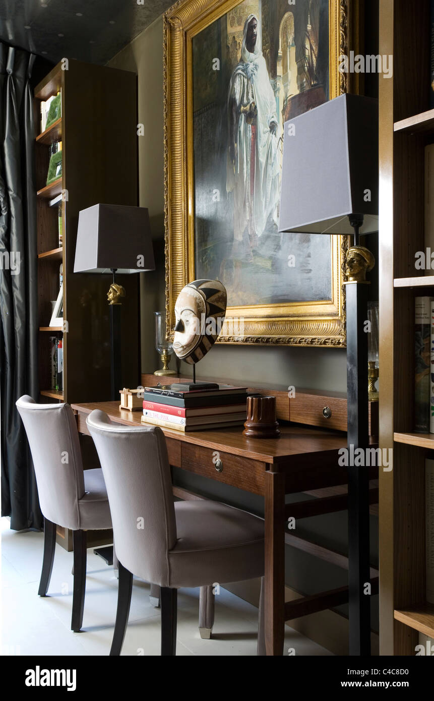 Gilt framed oil painting above wooden writing desk with mounted African mask and upholstered chairs - Stock Image