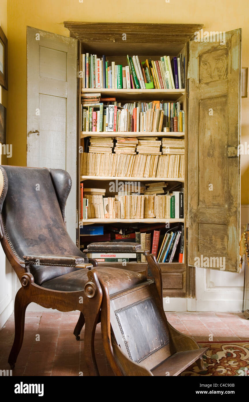 Antique Wooden Wingback Armchair With Leather Upholstery And Footrest In  Room With Rustic French Open Wooden Cupboard With Books
