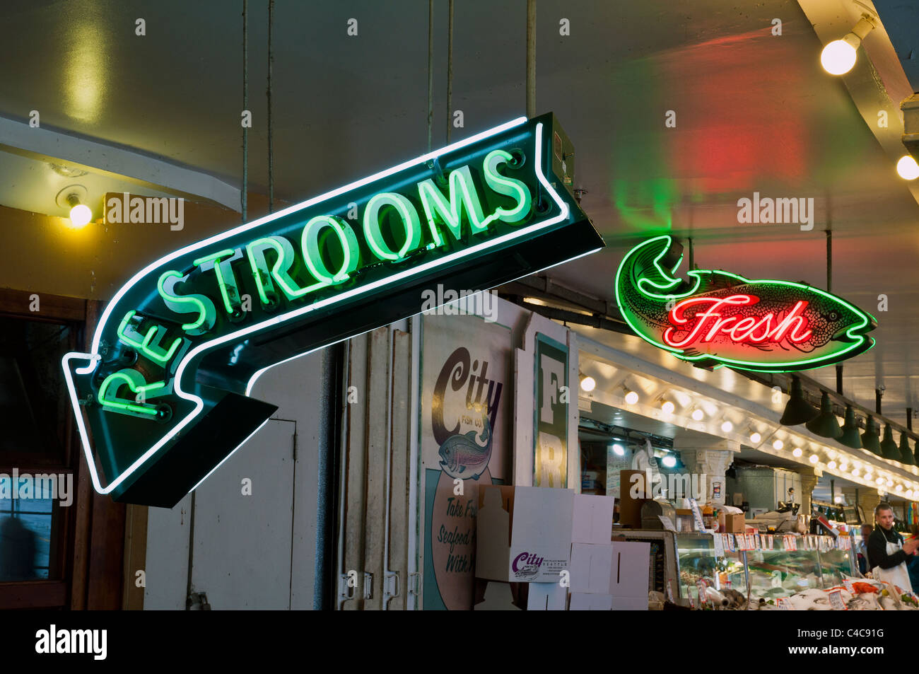 Neon signs indicating restrooms and fresh fish, Pike Place Market, Seattle, Washington, USA - Stock Image