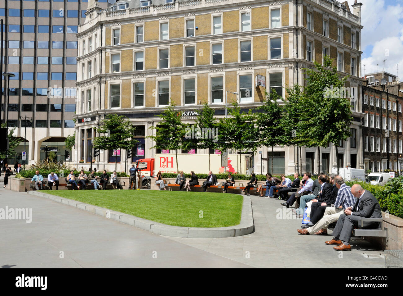 People enjoying the sunshine in a new, modern triangle shaped public seating area or open space Holborn Circus London - Stock Image