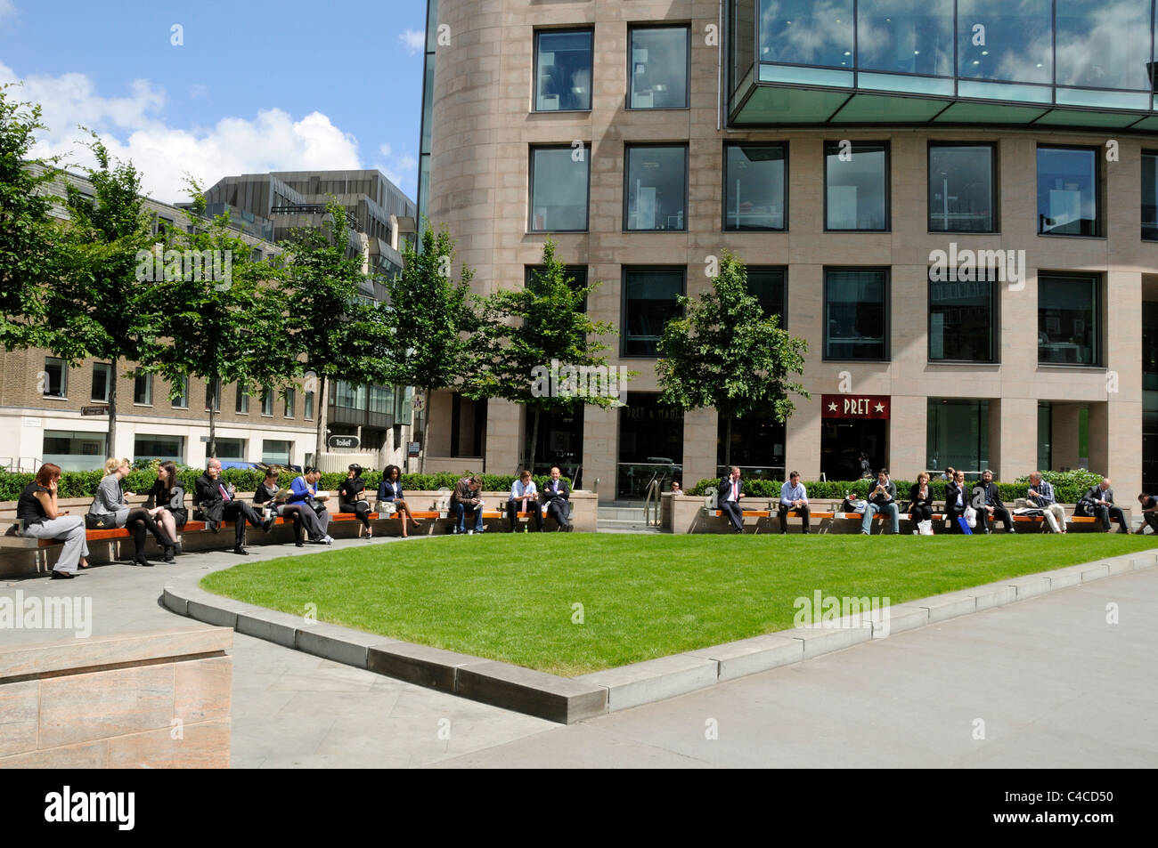 People enjoying the sunshine in a new modern triangle shaped public seating area or open space, Holborn Circus Viaduct - Stock Image