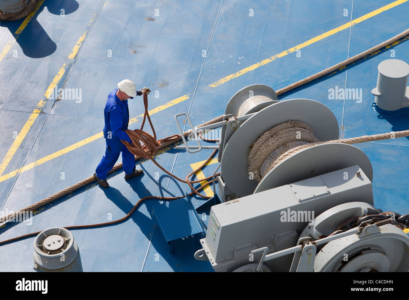 seaman seamen deckhands working work ship winch ropes warps Stock Photo