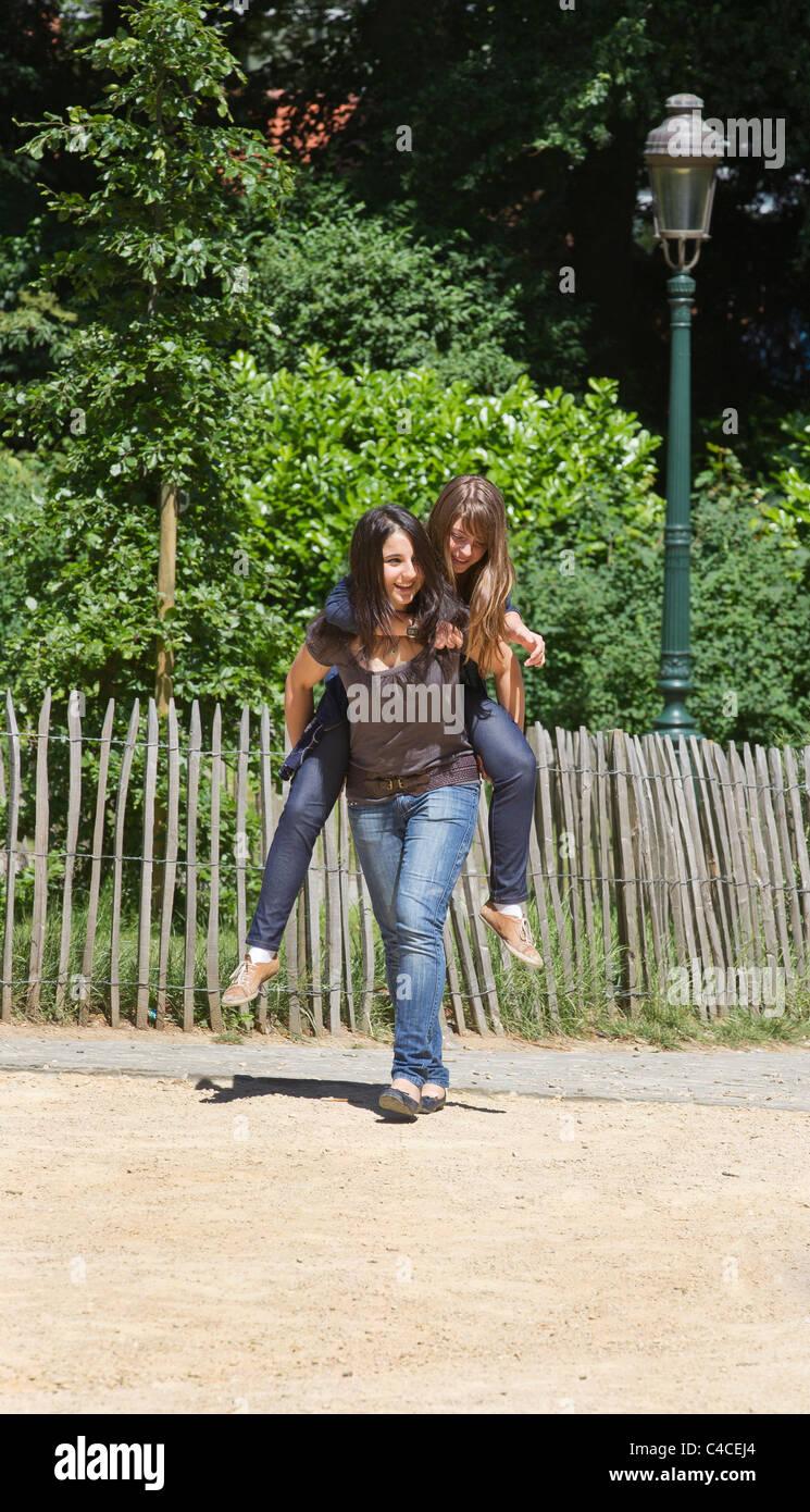 two girls playing piggyback - Stock Image