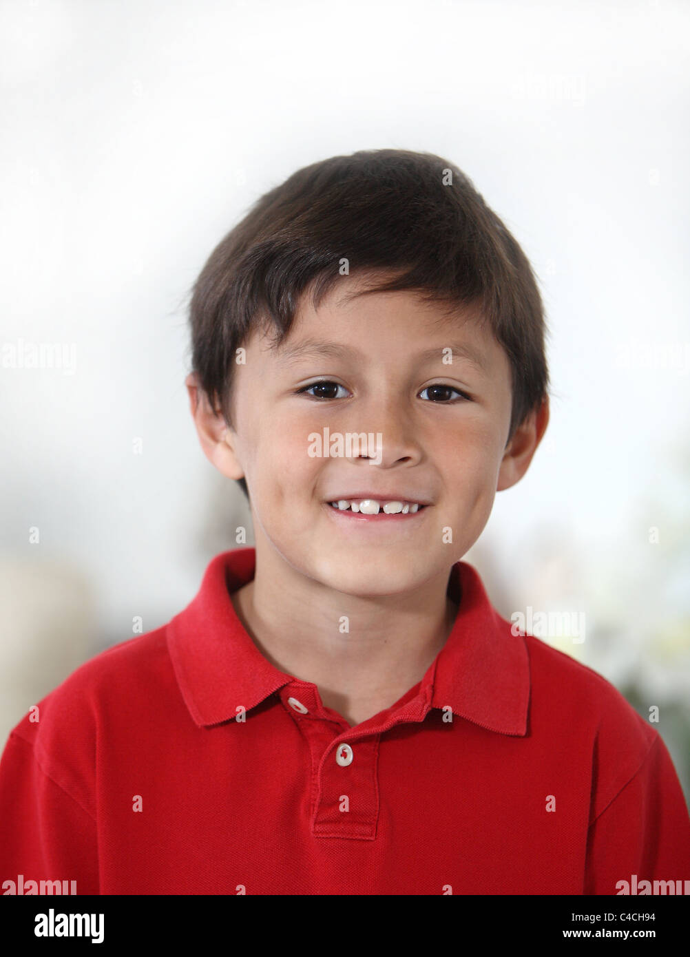Happy cheerful young Latino or Hispanic boy in red shirt against light background in portrait mode with copy space - Stock Image