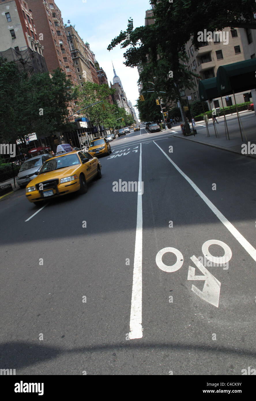 Cycle lane and cab on fifth avenue, near washington square park, New York - Stock Image
