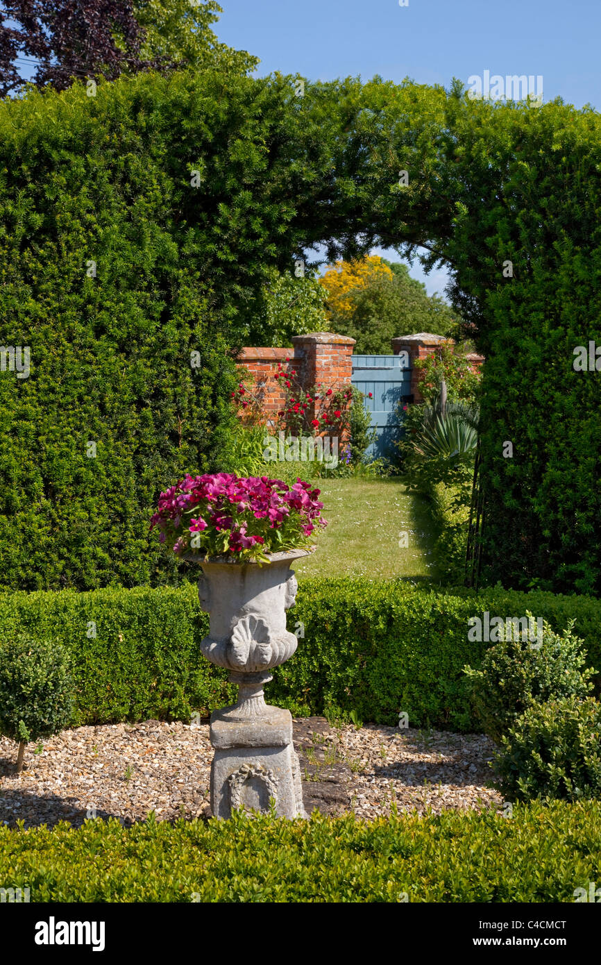 box hedging and yew hedge arch in garden with center piece urn leading to garden gate - Stock Image